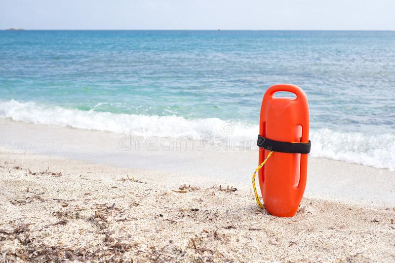 Orange buoy standing on the sand in front of the sea stock photography