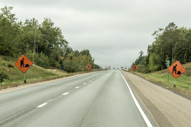 Orange byggnadsarbetaretecken på vägen in i avståndet på trans. Kanada royaltyfri foto