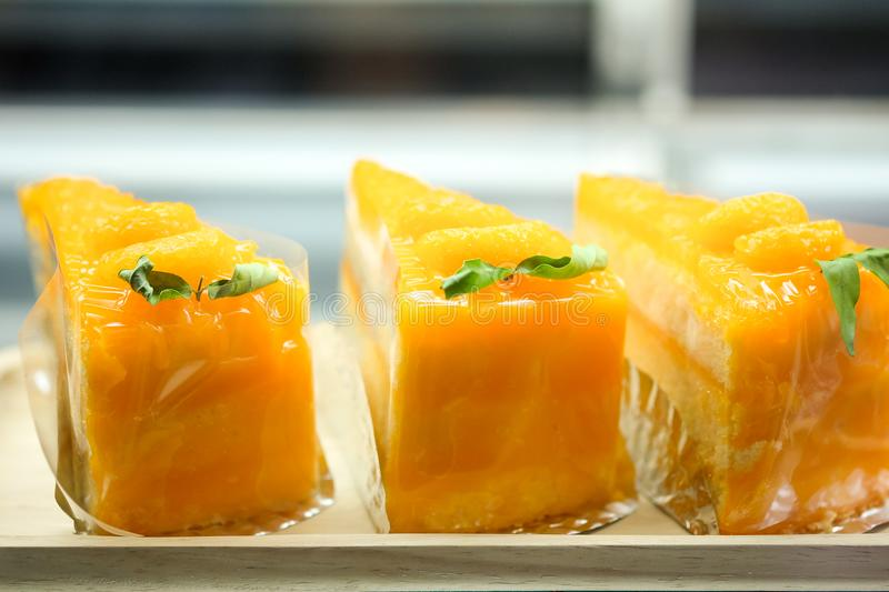 Orange cake is cut. In a glass refrigerator royalty free stock photo