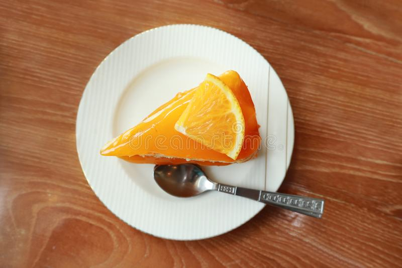 Orange cake on the saucer  on wooden table,tasty sweet dessert on dining table royalty free stock photos