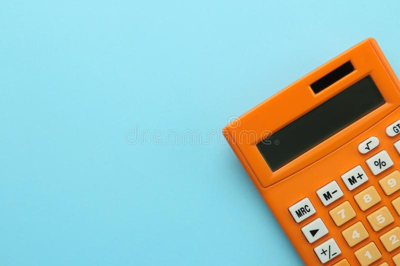 Orange calculator on a bright blue paper background. Office supplies. Education. back to school. top view. place for text stock photos