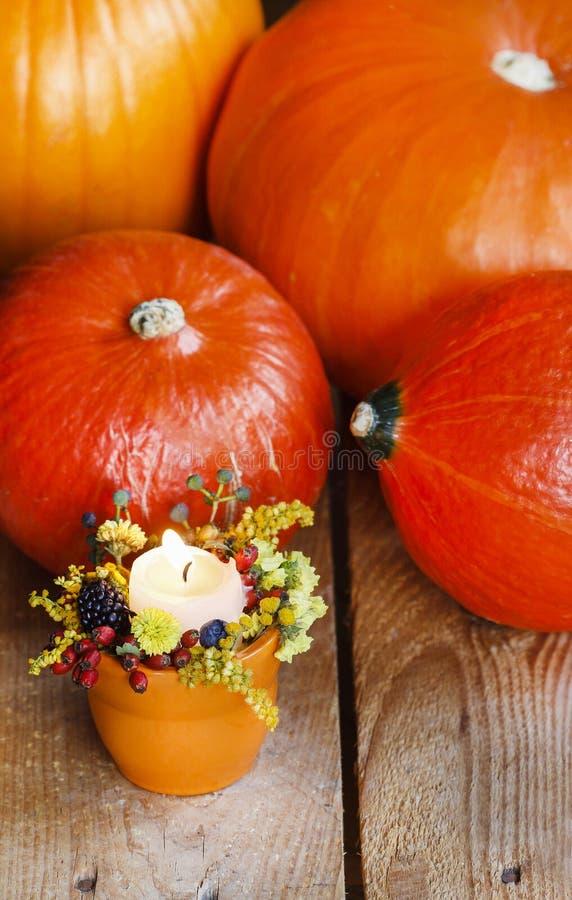 Orange candle holder with autumn flowers stock photo