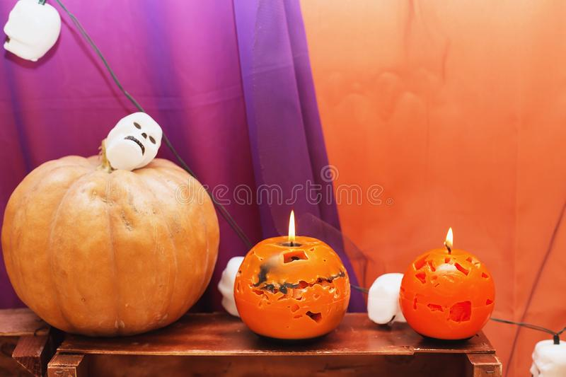 orange candles and Halloween pumpkin on textured surface in front of violet backdrop royalty free stock images