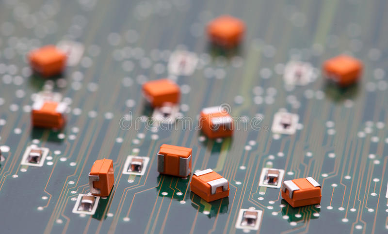 Orange capacitor on green pcb.  stock image