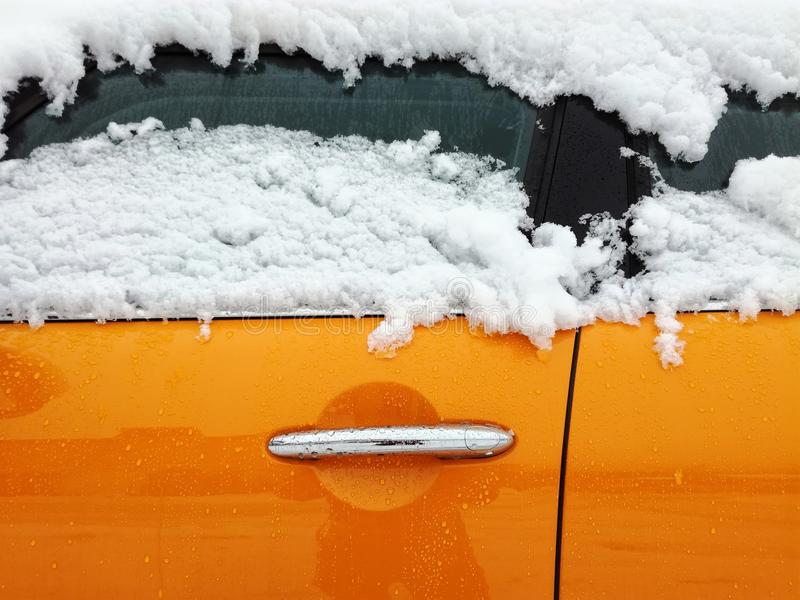 Orange car door. Close up of orange car covered with snow in winter stock images