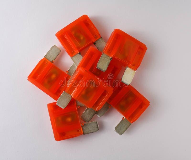 Orange car fuses on white background. Multiple orange car fuses on white background, close range view stock photography