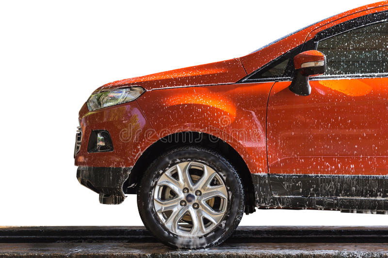 Orange car with white soap on the body in car care shop stock photo