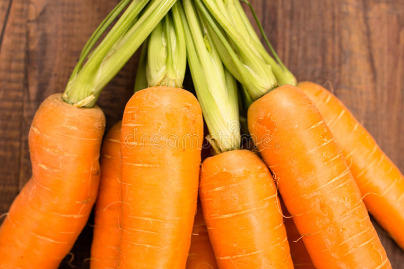 Orange carrots. With green on a wooden table royalty free stock photos