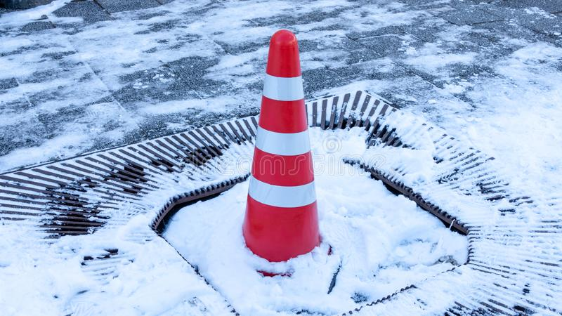Orange caution cone in snow. On sidewalk royalty free stock images