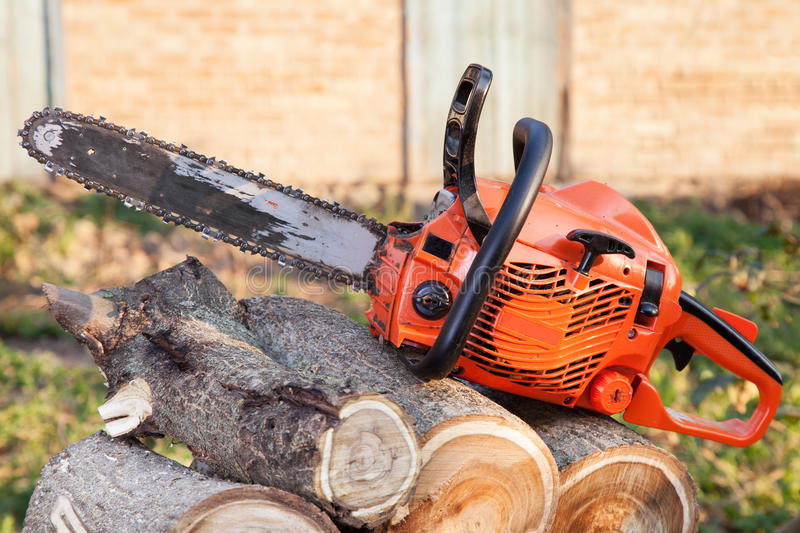 Orange chainsaw. The orange chainsaw lying on firewood outdoors royalty free stock image