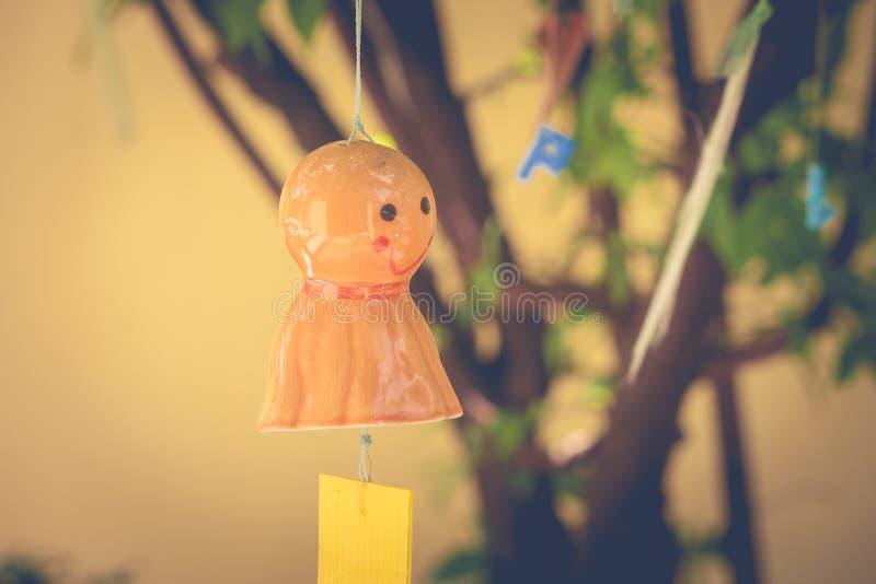 Orange chasing rain Japanese doll hanging on branches tree. royalty free stock image