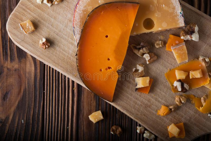 Orange cheese on a wooden board with nuts stock photography