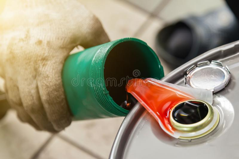 Orange chemical car wash flows from a canister into a green bottle. Paint for painting and building interiors and exteriors. Orange chemical car wash orange royalty free stock photos