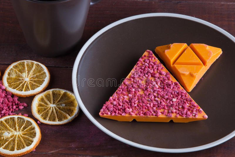 Orange chocolate with freeze-dried raspberries. On wood background with plate and slices of dried oranges royalty free stock image
