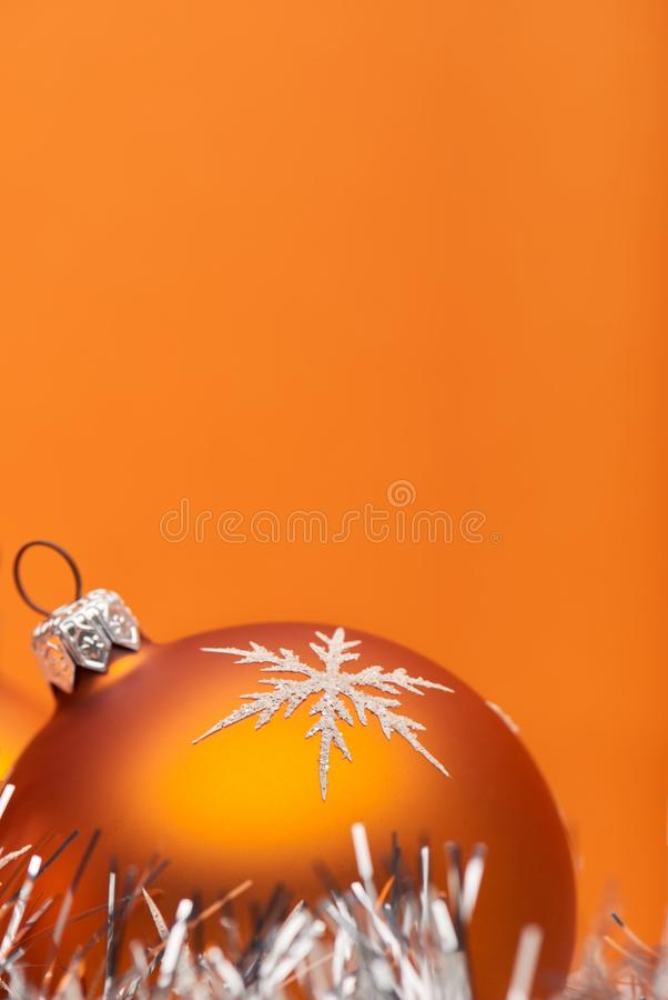 An orange Christmas bauble decoration adorned with a silver white snow flake on an orange background with room for custom text. Christmas themed graphic stock photography