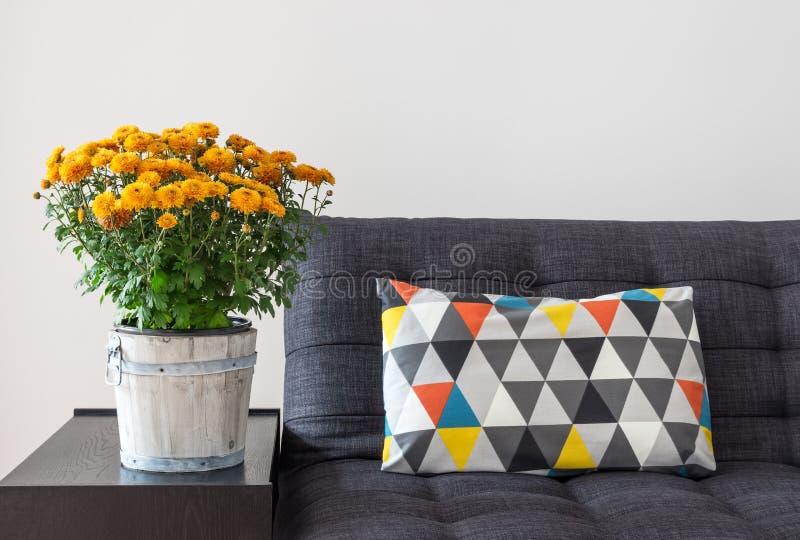 Orange chrysanthemums and bright cushion on a sofa stock photo