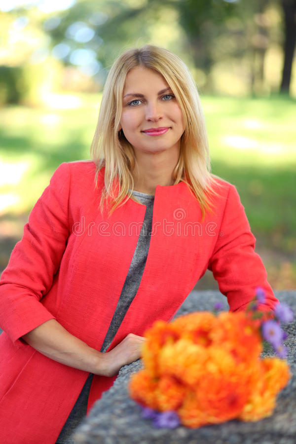 Orange coat. Cute young woman in park royalty free stock image