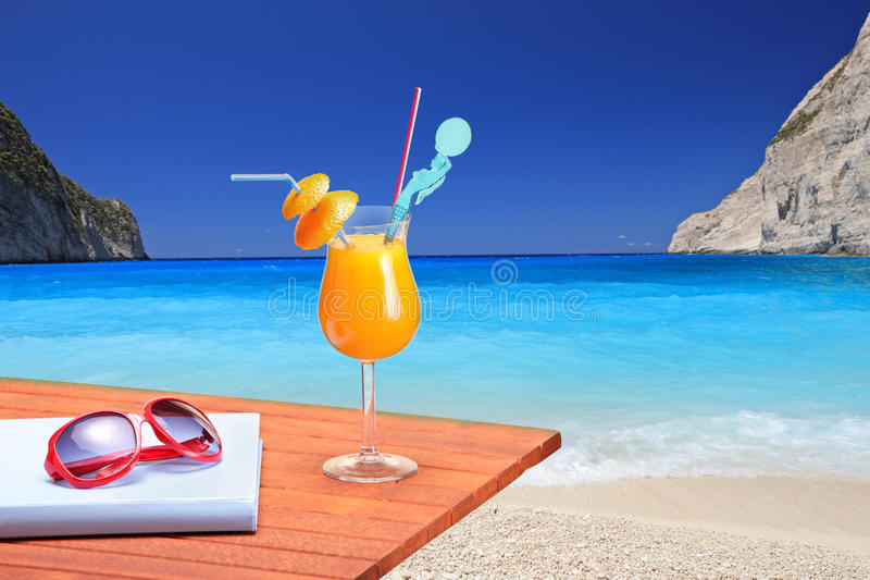 Orange cocktail on a beach table. At Navagio beach on Zakynthos island, Greece royalty free stock photo