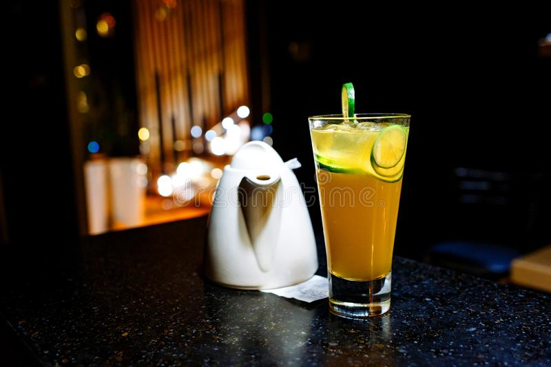 Orange cocktail with lime and teapot on dark background royalty free stock images