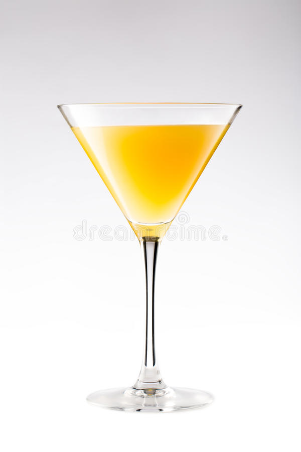 Orange cocktail in a martini glass on white. Background royalty free stock images
