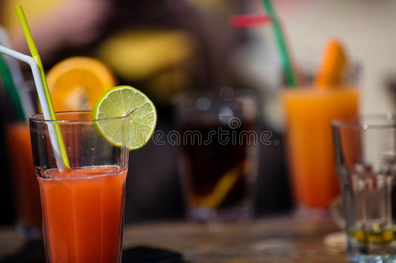 Alcohol orange daiquiri cocktail on beach bar. Orange cocktail on rustic wooden table.Alcohol bloody mary cocktail on beach bar wooden table royalty free stock images