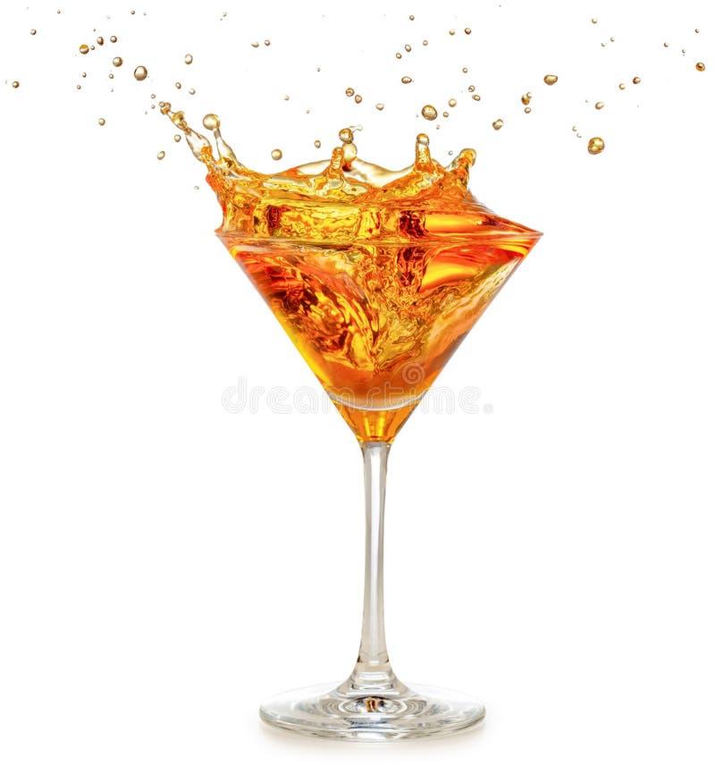 Orange cocktail splashing in martini glass. Isolated on white royalty free stock photography