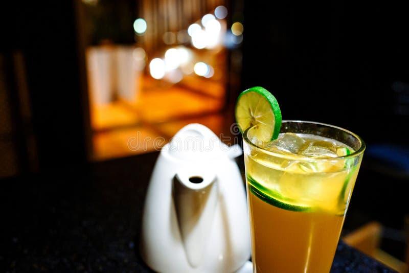 Orange coctail med limefrukt och tekannan p? m?rk bakgrund royaltyfri fotografi