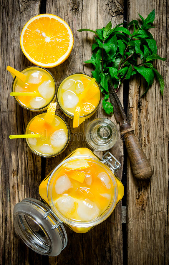 Orange coctail med vodka-, is- och mintkaramellsidor på en trätabell royaltyfri bild