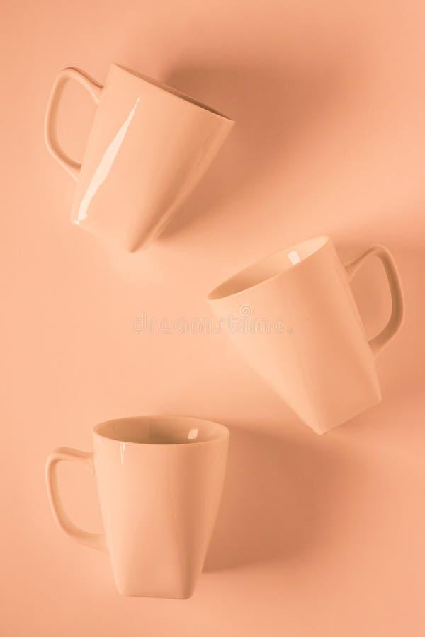 3 Orange coffee mugs on orange background scattered with empty copyspace. 3 monochromatic orange coffee mugs scattered on orange background with blank empty room stock image