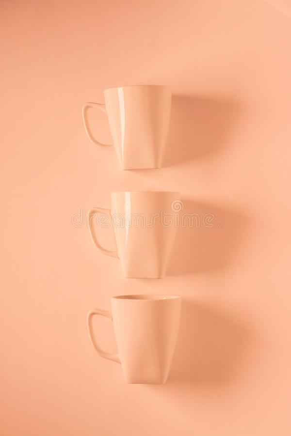3 Orange coffee mugs on orange background in a vertical row with empty copyspace. 3 monochromatic orange coffee mugs lined up in a row on orange background with royalty free stock image