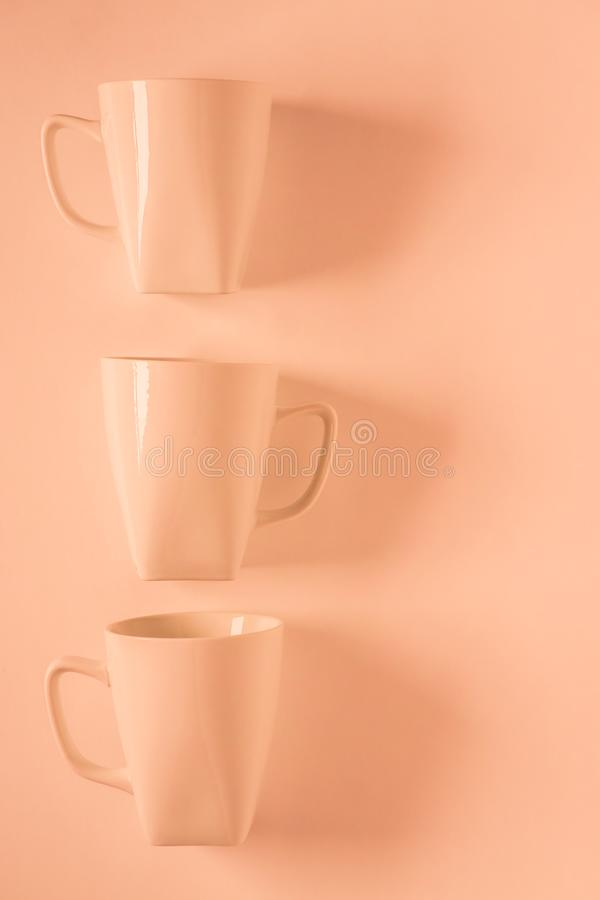 3 Orange coffee mugs on orange background in a vertical row with empty copyspace. 3 monochromatic orange coffee mugs lined up in a row on orange background with stock image
