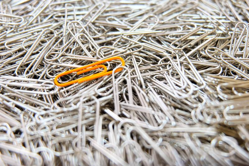 Orange paper clip on multiple paper clips background. Orange color paper clip on multiple paper clips background stock photo