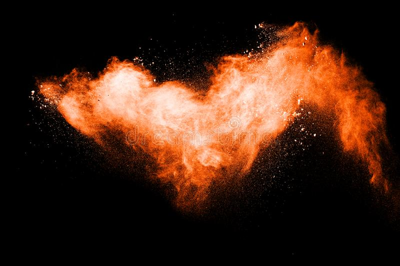 Orange color powder explosion on black background. Mauve orange color cloud. royalty free stock photos