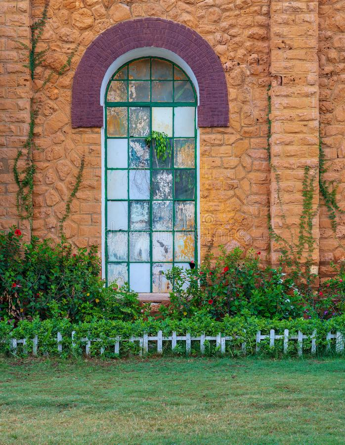 Orange colored bricks stone wall with big old grunge window covered with green metal grid, green grass floor, and plants at summer stock photography