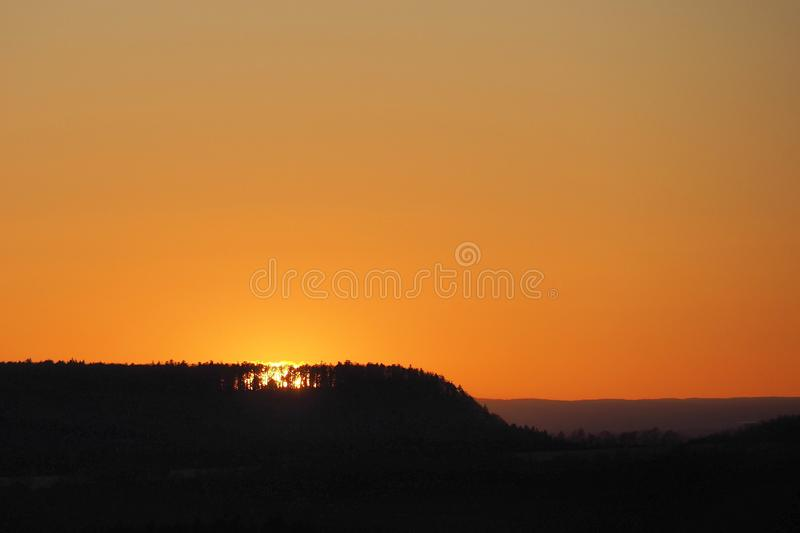 Orange colored sunset at the Swabian Alb, Germany. Sunset with orange color in the Swabian Alb in the southwest of Germany. The sun just vanished behind the hill royalty free stock images