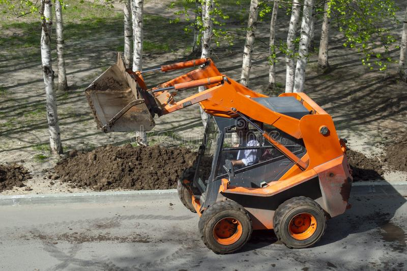 An orange-colored wheel loader delivers ground to an alley with trees royalty free stock images