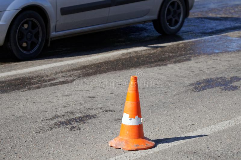 An orange cone stands on the road next to the wheels of a passing car. Life in the city. Daylight royalty free stock images