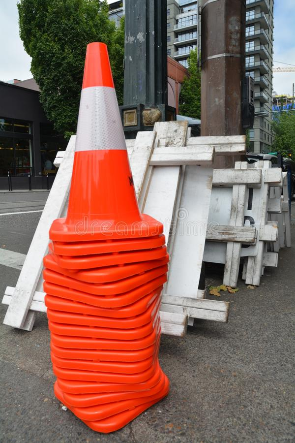 Orange cones and white barricades in Portland, OR. These are stacked orange safety cones and white barricades in downtown Portland, Oregon royalty free stock image