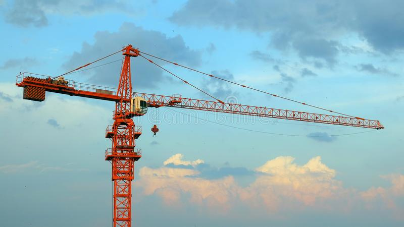 Ð¡onstruction crane against a background of beautiful cumulus clouds in summer. Orange construction crane against a background of beautiful cumulus clouds in royalty free stock photo