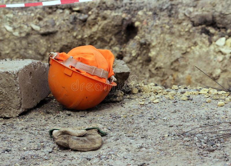orange construction helmet and mitten lies on the edge of the ditch, where the reconstruction works water pipes. stock photography