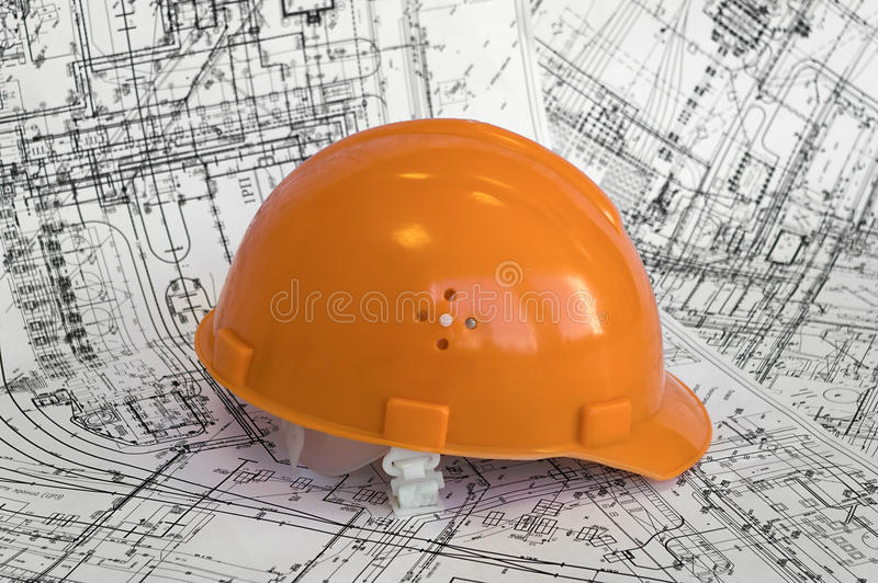 Orange constructional helmet and project drawings. stock photo