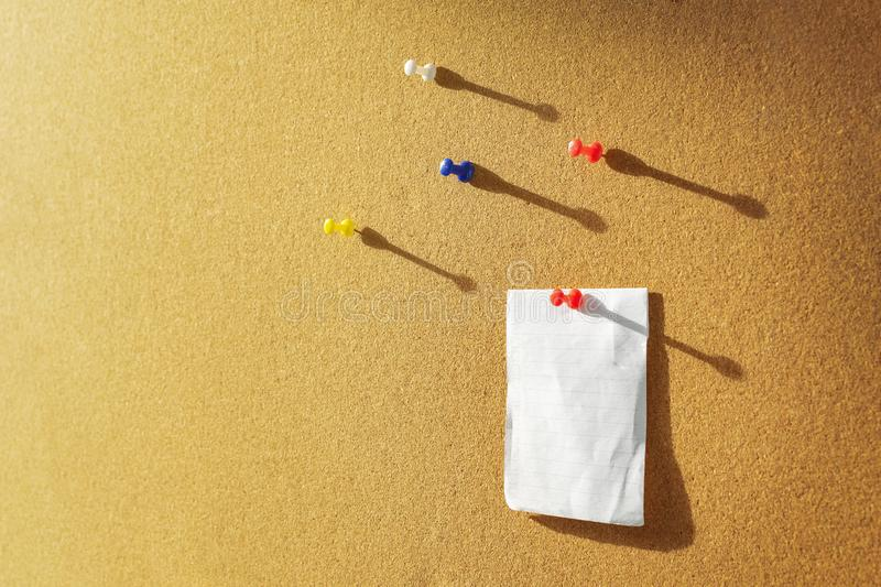 Orange Cork board with one bulletin paper note pinned and several different color pins above. Warm sunlight from the side royalty free stock image
