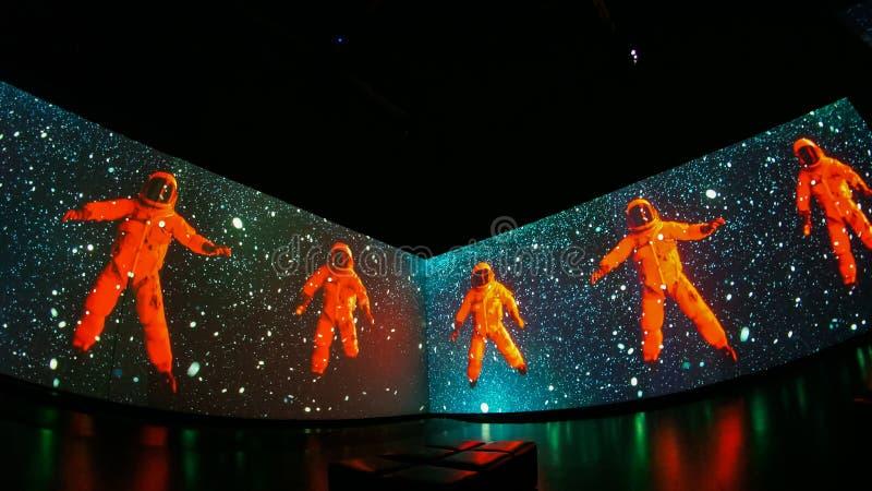Orange cosmonauts among stars in space. Human in stars stock photography