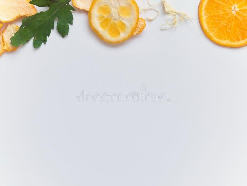Orange coupée en tranches et épluchée sur le fond blanc et disposé autour du cadre photos stock