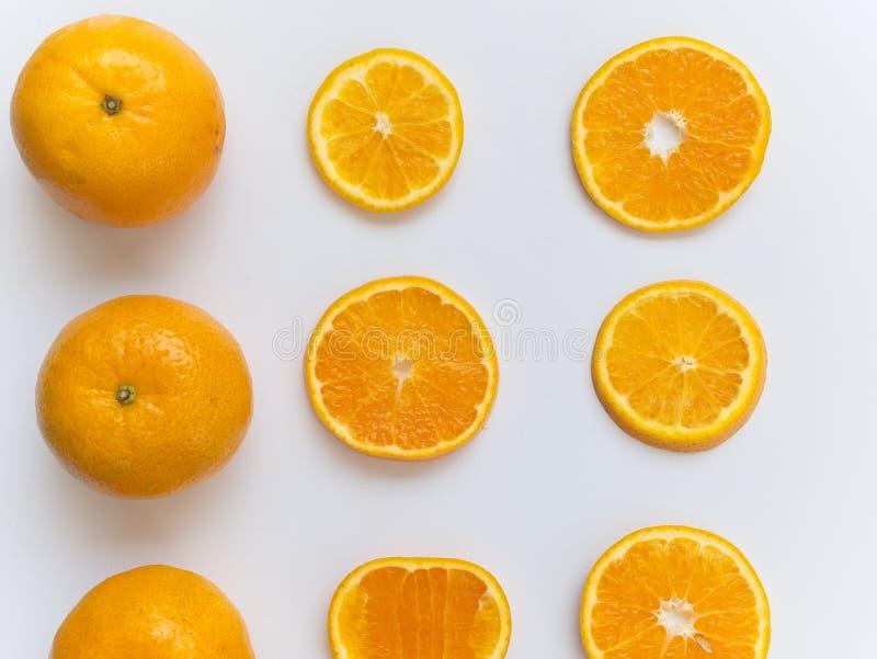 Orange coupée en tranches et entière sur le fond blanc et disposé autour du cadre image stock