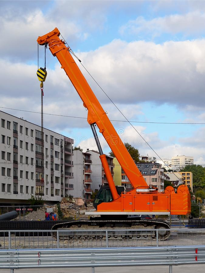 Orange crawler crane at the site of road construction works in the city against the background of a residential building and the s stock photos