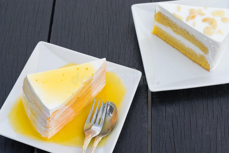 Orange crepe cake in white dish on black wooden table royalty free stock photo