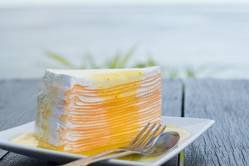 Orange crepe cake in white dish on black wooden table with sea background stock image