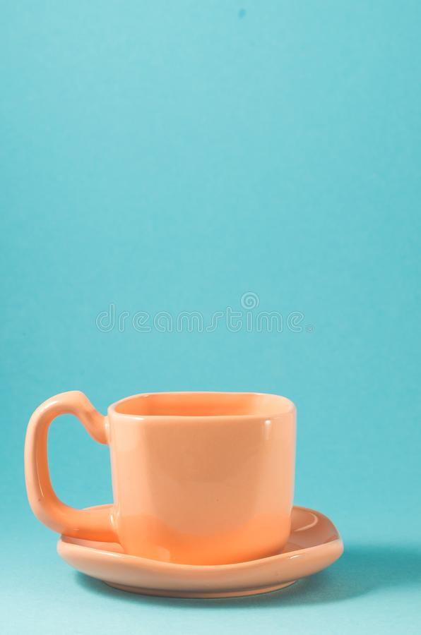 Orange cup on a blue background/orange cup with a saucer on a blue background. Coffee full black view top energy hot drink breakfast closeup beverage above rown royalty free stock photography