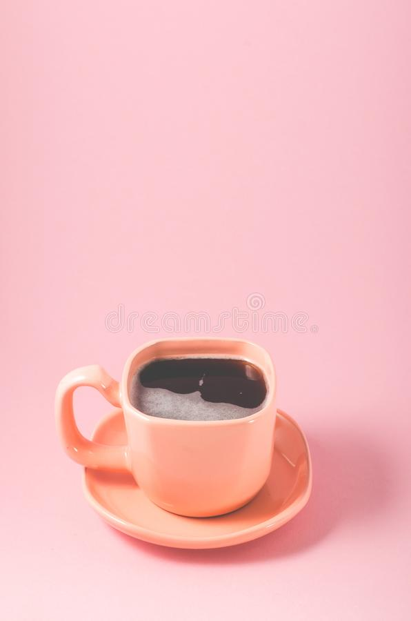 Orange cup of espresso on a pink background/orange cup of espresso with a foam on a pink background with copy space. Coffee oink full black view top energy hot royalty free stock images
